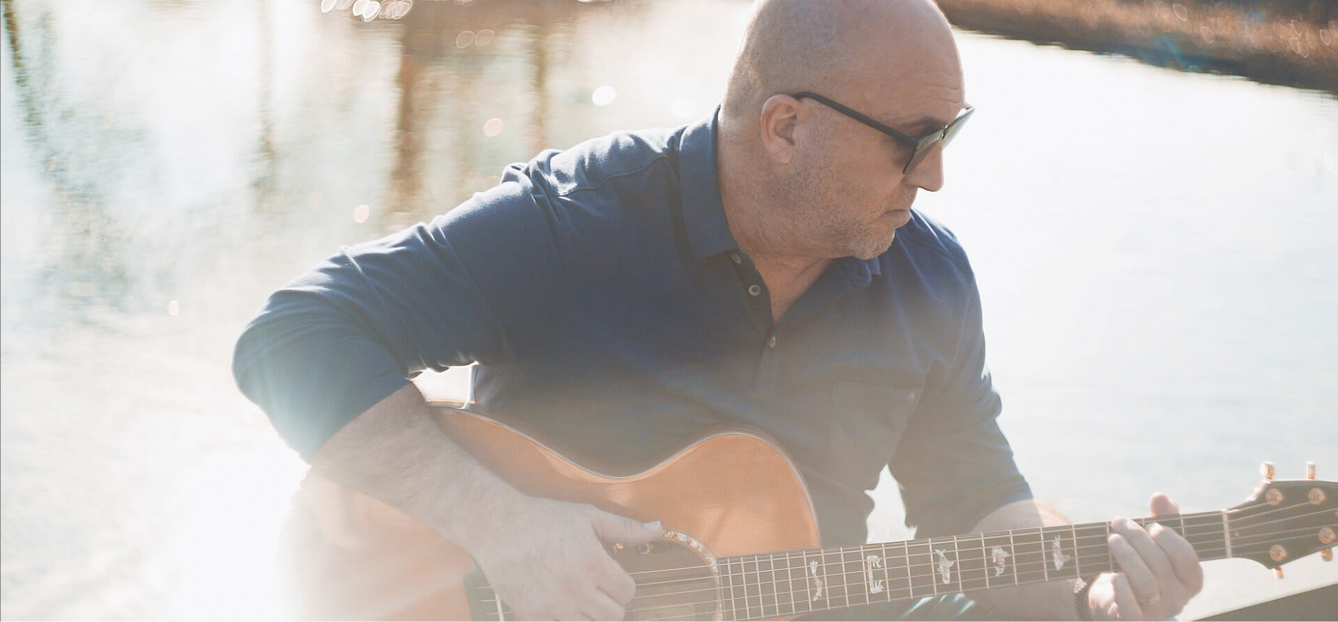 John Tracy sitting by the water playing the guitar