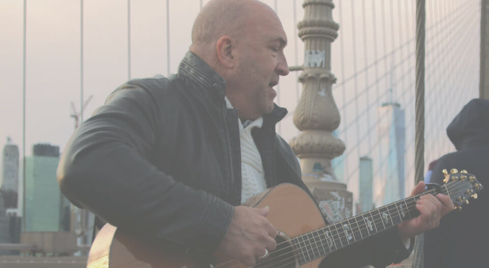 John Tracy playing guitar on brooklyn bridge